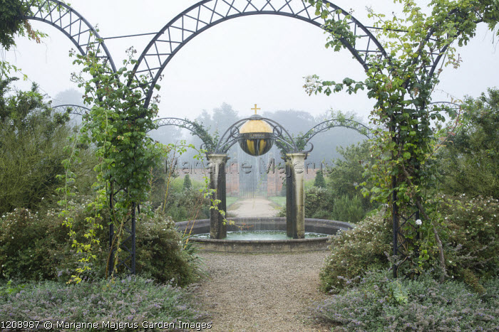 Climbers scrambling over metal arch, orb water feature, circular pool, Queen Elizabeth II Golden Jubilee fountain