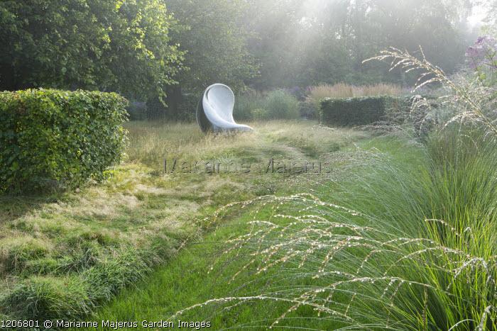 Sculpture by Ron Arad in long grass meadow, Molinia caerulea subsp. caerulea 'Heidebraut'