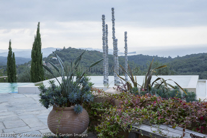 Contemporary aluminium sculpture, 'Towers of Time', in infinity pool, view to sea, Euphorbia characias subsp. wulfenii, Phormium tenax, Trachelospermum jasminoides, Strelitzia reginae in pot