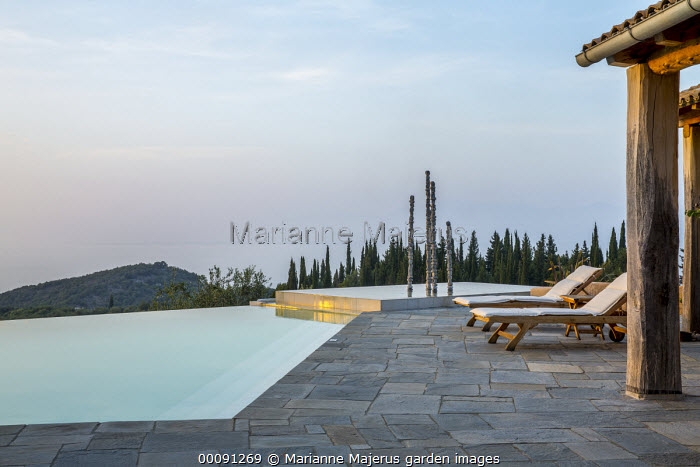 Recliner chairs on infinity pool terrace, aluminium sculpture, 'Towers of Time'