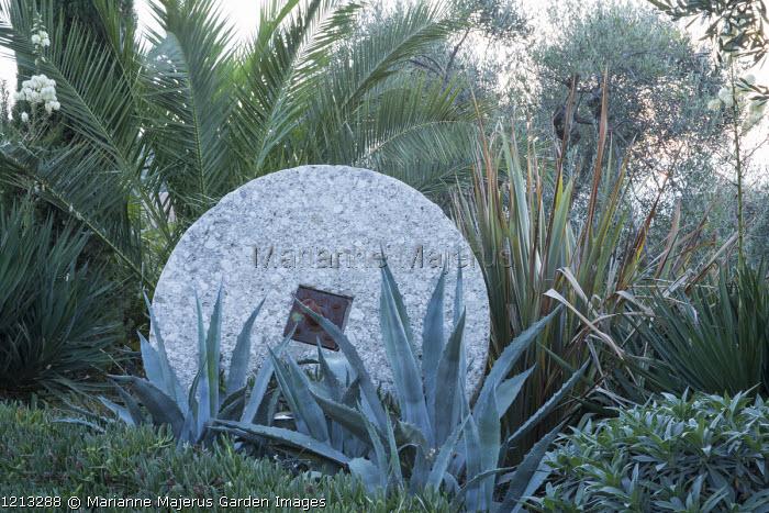 Old mill stone in border, Phoenix canariensis, Agave americana, Phormium tenax, Carpobrotus edulis