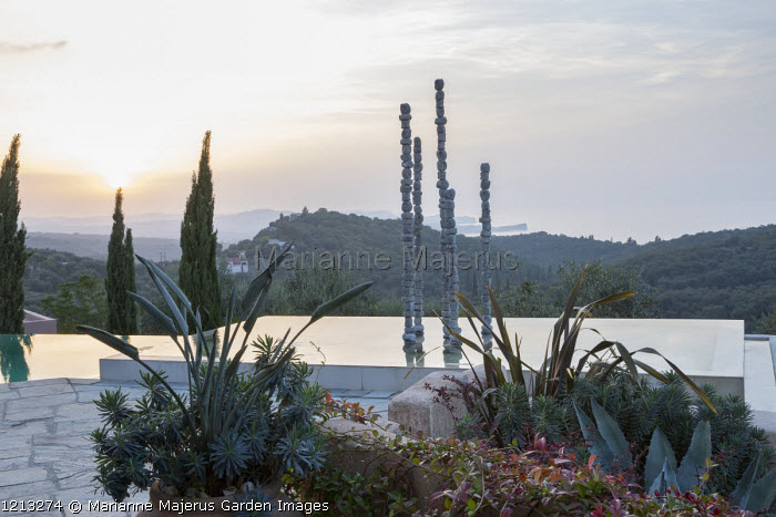 Aluminium sculpture, 'Towers of Time', in infinity pool at sunset, view to Cape Drastis, Strelitzia reginae and Euphorbia characias subsp. wulfenii in pot, Phormium tenax, Agave americana.