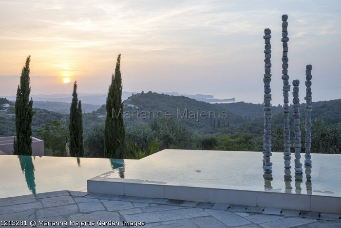 Aluminium sculpture, 'Towers of Time' by Katherine Wise, in infinity pool at sunset, view to Cape Drastis
