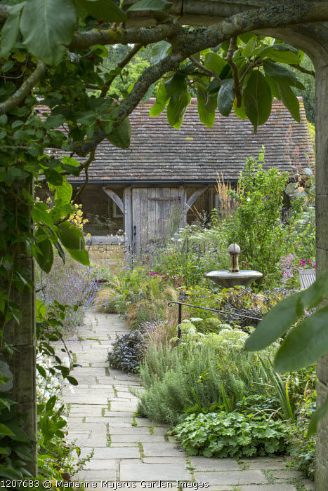 View through stone arch into secret garden, water fountain, stone paving, Alchemilla mollis, sage, ammi