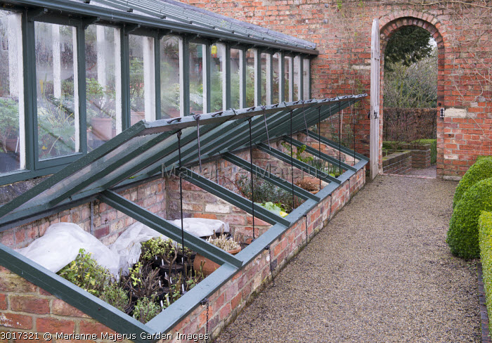 Cold frames and greenhouse, arch-topped gate in wall, gravel