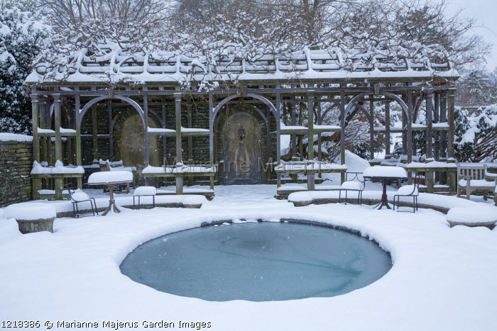 Wooden pergola, frozen circular pool, snow-covered tables and chairs