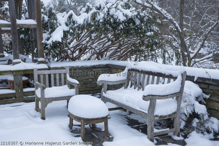 Snow-covered bench, chair and table on patio