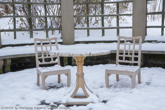 Table and chairs on snow-covered patio