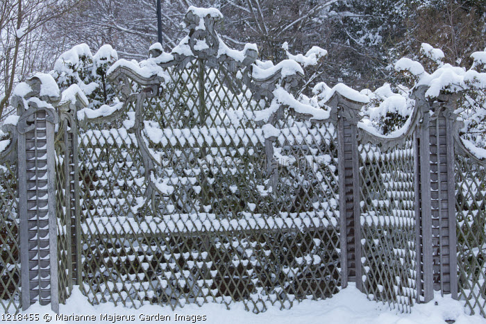 Ornate trellis screen covered in snow