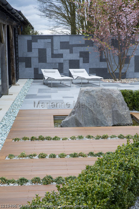 Contemporary recliner chairs on flamed grey and black granite paved patio, stone wall, Balau hardwood decking with Ophiopogon japonicus 'Minor' in rills, large granite rock, Prunus 'Accolade', box hedge