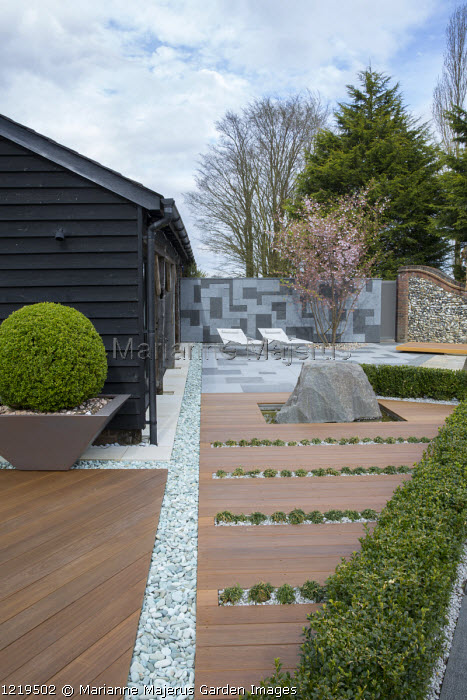 Contemporary recliner chairs on flamed grey and black granite paved patio, stone wall, Balau hardwood decking with Ophiopogon japonicus 'Minor' in rills, large granite rock, Prunus 'Accolade', box hedge, large box ball in container, granite chippings rill