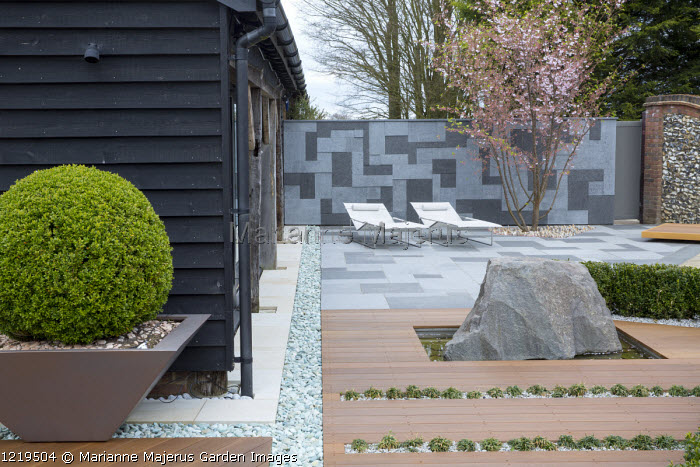 Contemporary recliner chairs on flamed grey and black granite paved patio, stone wall, Balau hardwood decking with Ophiopogon japonicus 'Minor' in rills, large granite rock, Prunus 'Accolade', large box ball in container