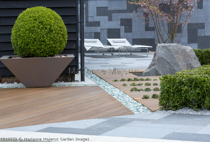 Contemporary recliner chairs on flamed grey and black granite paved patio, stone wall, Balau hardwood decking with Ophiopogon japonicus 'Minor' in rills, large granite rock, Prunus 'Accolade', low clipped box hedge, large box ball in pot, granite chippings rill