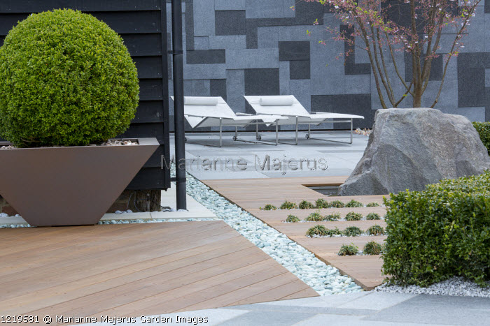 Contemporary recliner chairs on flamed grey and black granite paved patio, stone wall, Balau hardwood decking with Ophiopogon japonicus 'Minor' in rills, large granite rock, Prunus 'Accolade', large box ball in pot, granite chippings rill