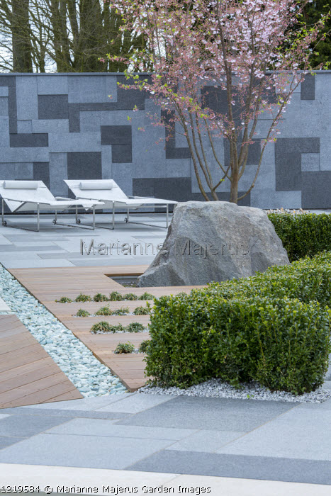 Contemporary recliner chairs on flamed grey and black granite paved patio, stone wall, Balau hardwood decking with Ophiopogon japonicus 'Minor' in rills, large granite rock, Prunus 'Accolade', pebble rill