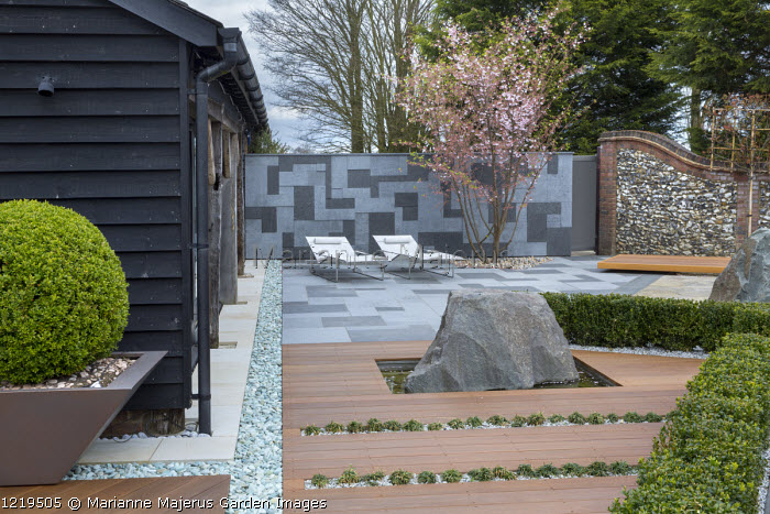 Contemporary recliner chairs on flamed grey and black granite paved patio, stone wall, Balau hardwood decking with Ophiopogon japonicus 'Minor' in rills, large granite rock, Prunus 'Accolade', low clipped box hedge, large box ball in container