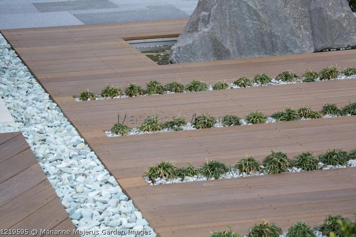 Balau hardwood decking with Ophiopogon japonicus 'Minor' in rills, large granite rock, pebble rill