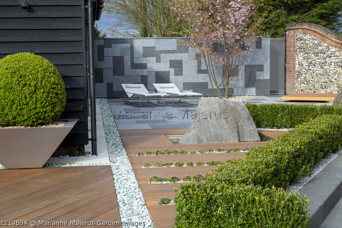 Contemporary recliner chairs on flamed grey and black granite paved patio, stone wall, Balau hardwood decking with Ophiopogon japonicus 'Minor' in rills, large granite rock, Prunus 'Accolade', large box ball in container, granite chippings, low clipped box hedge