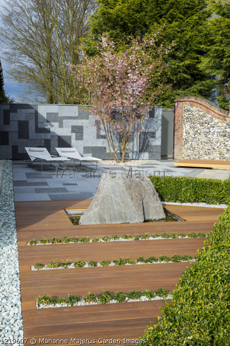 Contemporary recliner chairs on flamed grey and black granite paved patio, stone wall, Balau hardwood decking with Ophiopogon japonicus 'Minor' in rills, large granite rock, Prunus 'Accolade', low clipped box hedge