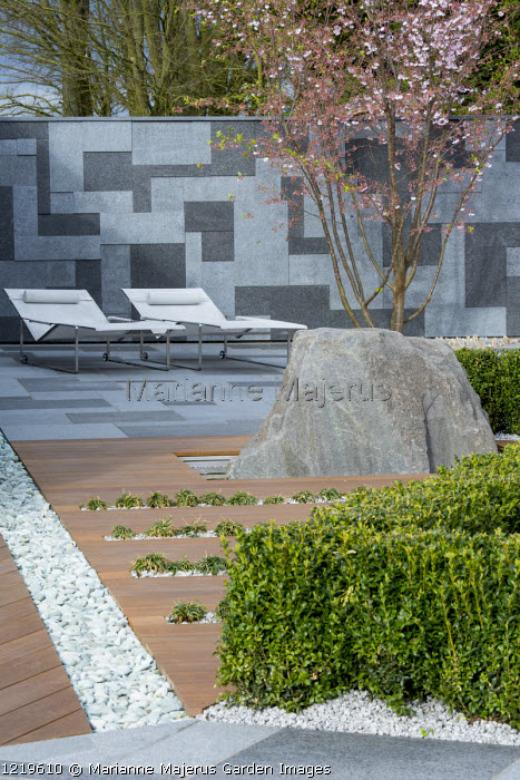Contemporary recliner chairs on flamed grey and black granite paved patio, stone wall, Balau hardwood decking with Ophiopogon japonicus 'Minor' in rills, large granite rock, Prunus 'Accolade', box hedge, pebble rill