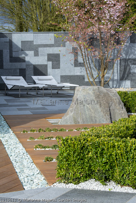 Contemporary recliner chairs on flamed grey and black granite paved patio, stone wall, Balau hardwood decking with Ophiopogon japonicus 'Minor' in rills, large granite rock, Prunus 'Accolade', low clipped box hedge, pebble rill