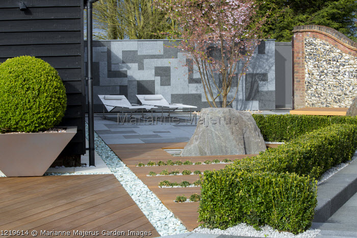 Contemporary recliner chairs on flamed grey and black granite paved patio, stone wall, Balau hardwood decking with Ophiopogon japonicus 'Minor' rills, large granite rock, Prunus 'Accolade', low clipped box hedge, large box ball in pot