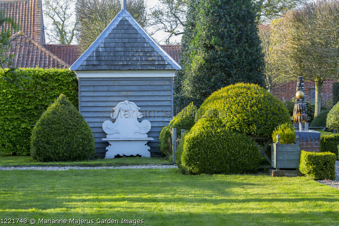 View across lawn to Baroque bench against wooden shed