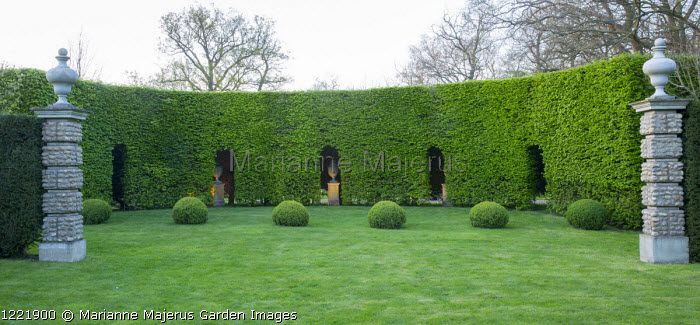 Formal garden, large box balls in lawn, urns on plinths in niches in hornbeam hedge