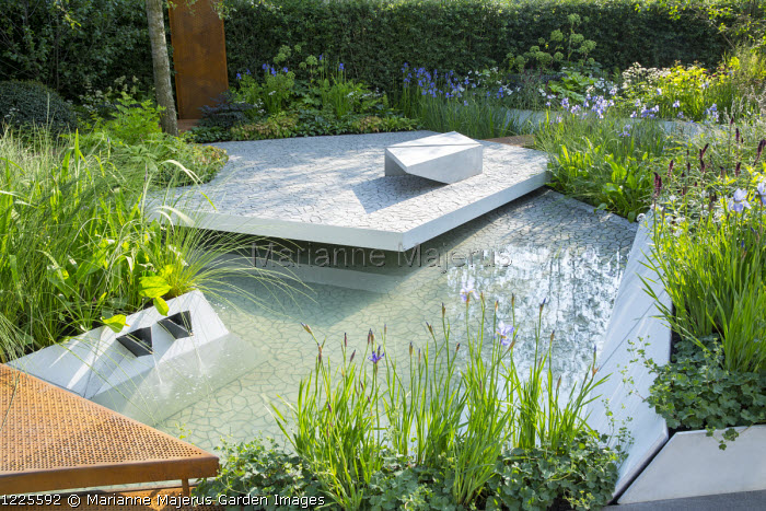 'Floating' patio, contemporary bench on cracked earth tile paving by KAZA Concrete designed by Edward Forster, Iris 'Gerald Darby', pond