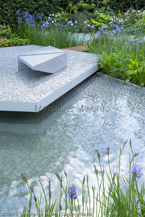 'Floating' patio, contemporary bench on cracked earth tile paving by KAZA Concrete designed by Edward Forster, Iris 'Gerald Darby', pond, Iris sibirica 'Perry's Blue'