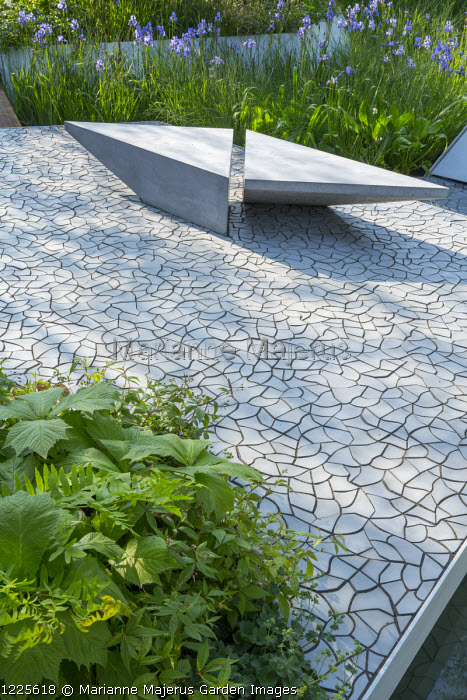 Contemporary bench on cracked earth tile paving by KAZA Concrete designed by Edward Forster, Iris sibirica 'Perry's Blue'
