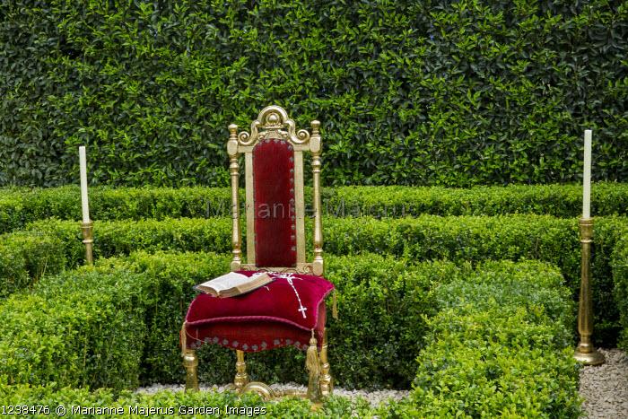 Clipped box hedges around ornate chair, Prunus lusitanica hedge