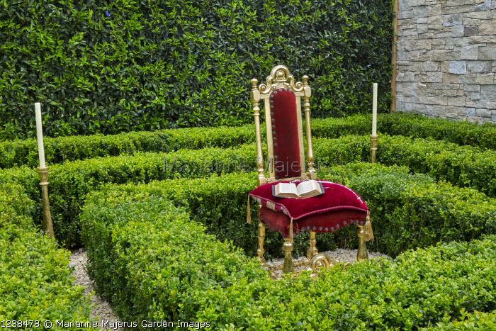 Clipped box hedges around ornate chair, Prunus lusitanica hedge