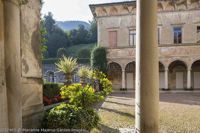 Portico around stone courtyard, fresco wall paintings, phormiums in stone urns