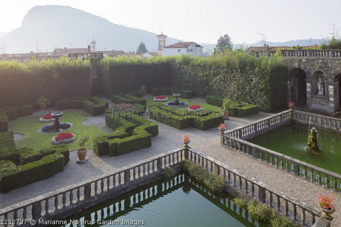 View across formal Mediterranean garden, clipped box parterre, square pools with stone balustrades