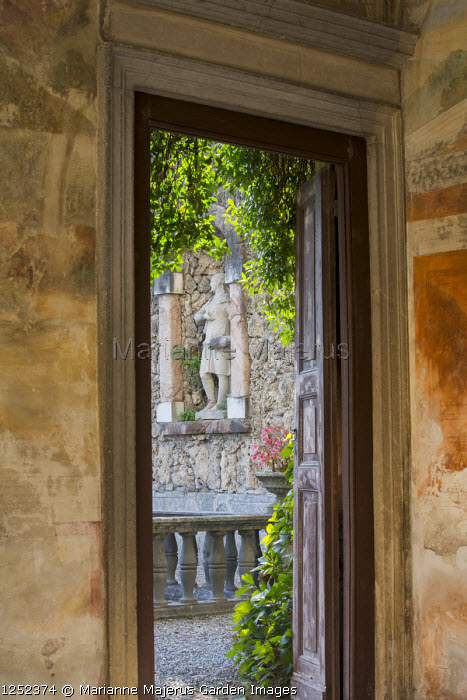 View through doorway to stone statue in wall niche
