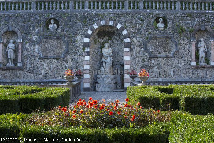 Dahlia in clipped box parterre, statues in arched wall niches, tufa wall
