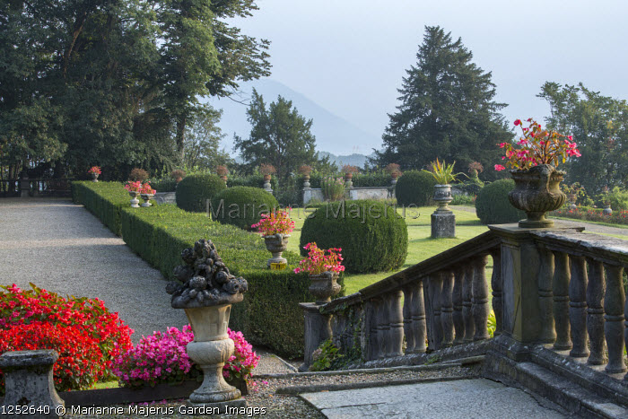 Stone balustrade, stone urns, clipped box hedges and domes in lawn
