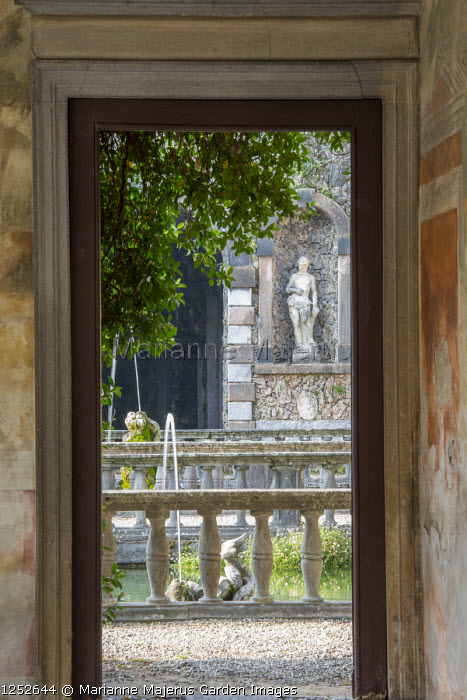 View through doorway to stone statue in wall niche, water fountains, stone balustrades
