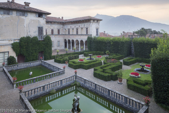 View across formal Mediterranean garden, clipped box parterre, square pools with stone balustrade