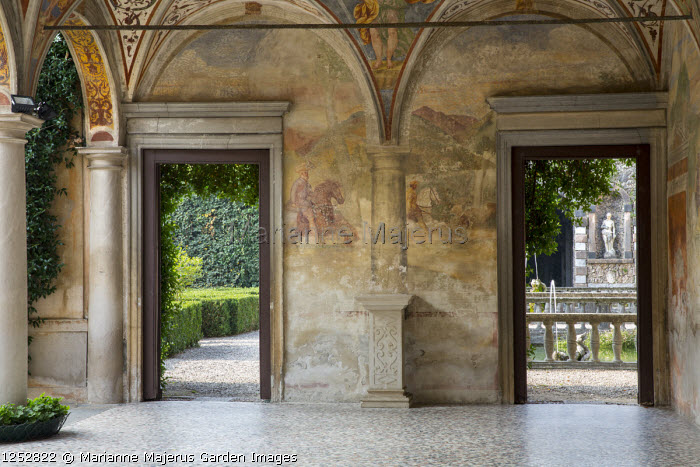 Interior of portico, doorways leading to mediterranean garden, stone balustrade, statue in wall niche, wall frescoes
