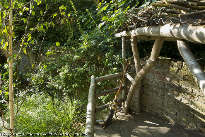 Wooden treehouse, brick wall, broom, Anemanthele lessoniana