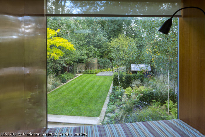 View from inside house with copper-clad walls through glass window to contemporary garden outside