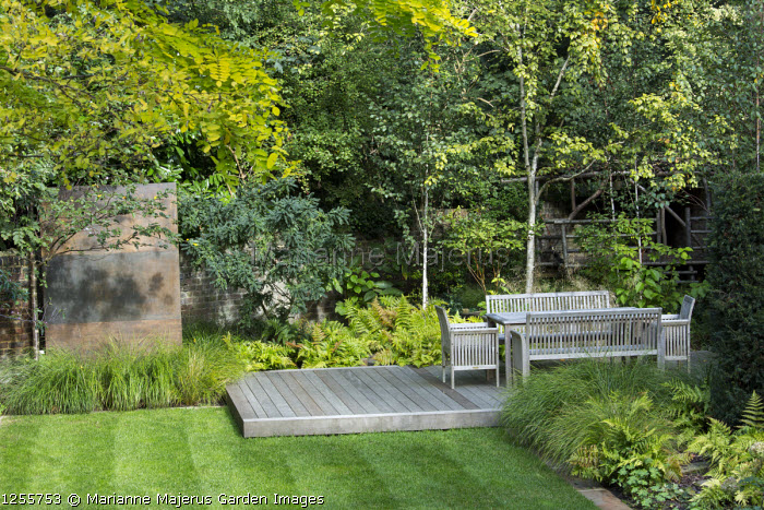 Wooden table and chairs on decking, copper-clad wall, Betula utilis var. jacquemontii, Anemanthele lessoniana