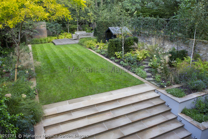 Overview of autumnal town garden, formal rectangular lawn edged with stone, Yorkstone steps