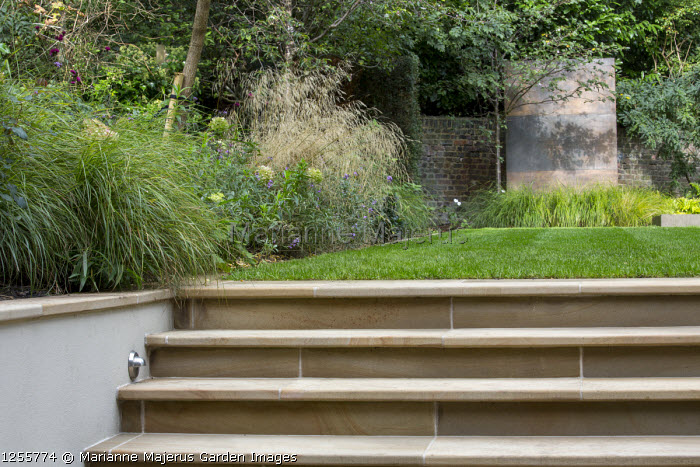 Yorkstone steps leading to raised lawn, Anemanthele lessoniana, Deschampsia cespitosa, copper-clad wall, Anemanthele lessoniana