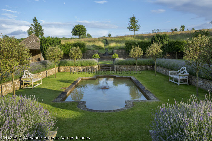 Formal pool and fountain in sunken garden, Lavandula angustifolia 'Princess Blue', stone wall, wooden Lutyens benches, standard Malus 'Evereste' trees