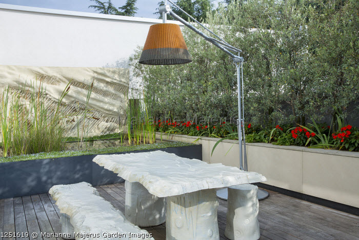"""Table and benches designed by Gaetano Pesce on decking under suspended contemporary lamp, raised pond, Olea europaea 'Cipressino' screen underplanted with Impatiens New Guinea Group, """"La Tempesta"""" (1981) wall art by Francesco Somaini"""
