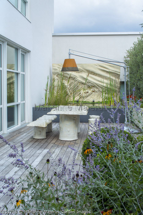 "Contemporary terrace, suspended lamp over table, benches and stools designed by Gaetano Pesce, raised pond, Perovskia atriplicifolia, ""La Tempesta"" (1981) wall art by Francesco Somaini"