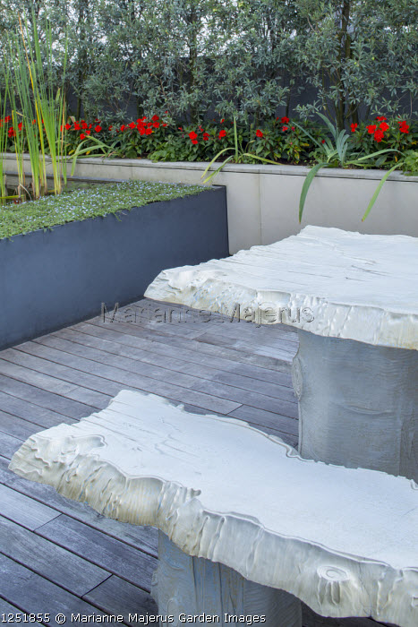 Table and benches designed by Gaetano Pesce on decking, Olea europaea 'Cipressino' screen in raised bed, raised pond